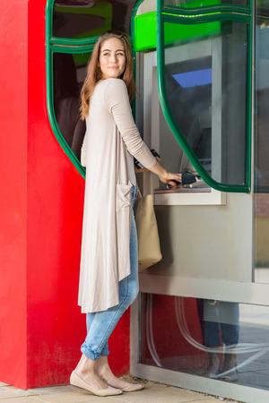 automatic transaction machine: Mujer bonita joven en un cajero automático Foto de archivo