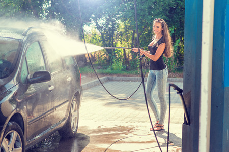 woman washing hair: Pretty woman in the car wash - hand wash Stock Photo