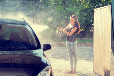 wash: Pretty woman in the car wash - hand wash Stock Photo