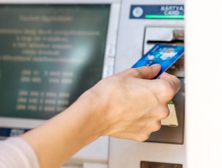 automatic transaction machine: Mano femenina - close up - retiros de efectivo en cajeros automáticos