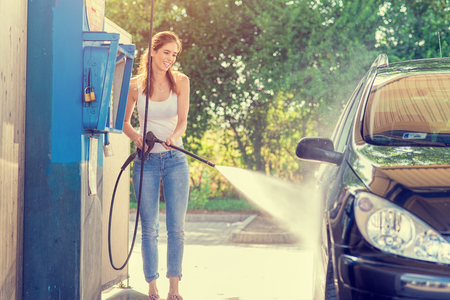clean car: Pretty woman in the car wash - hand wash Stock Photo