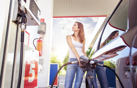 refuel: Pretty young woman refuel the car Stock Photo