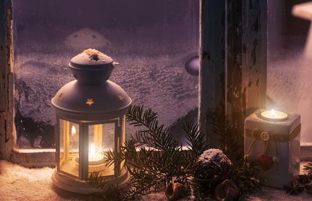 Kerstmis - kaarsen glow in the stomende venster