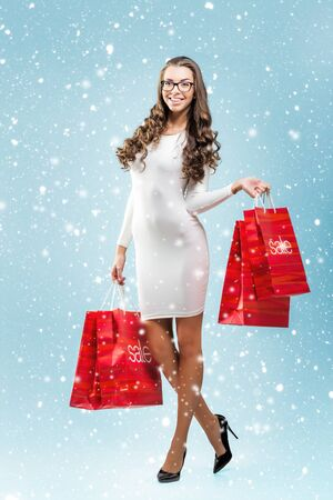 rebates: Pretty woman holding Bag Sale - snow background