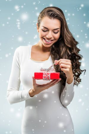 rebates: Woman surprised holding a red gift box