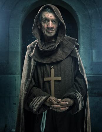 古い壁の正面に木製の十字架を保持している修道士