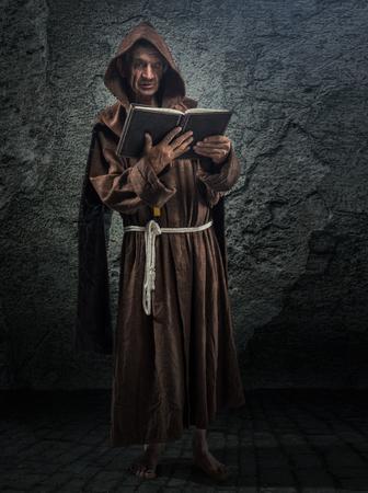 cristianismo: monje mayor, sacerdote tiene en su mano la Biblia Foto de archivo