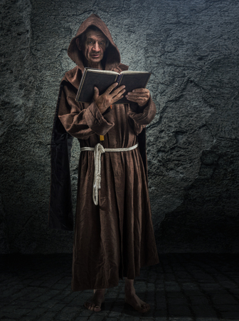 Senior monk, priest holds in his hand the Bible