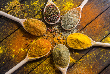 different spices in wooden spoons on a black wooden background like Pepper, coriander, dried vegetables and other