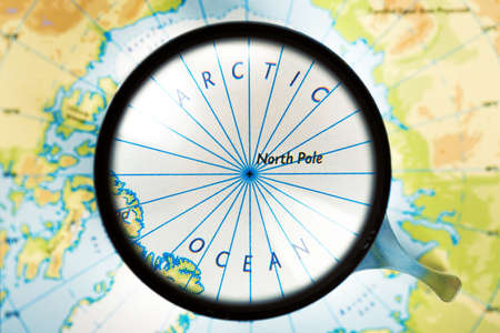 north pole: Map and magnifying glass. Arctic ocean and North Pole are on the focus. Stock Photo