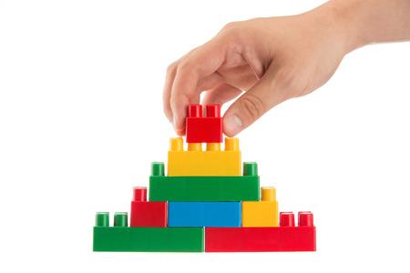비즈니스 개념, 흰색 배경에 플라스틱 빌딩 블록으로 벽을 구축하는 사람