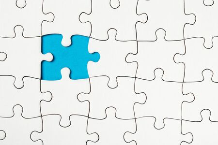missing piece: Missing piece in a puzzle on blue background, business conception