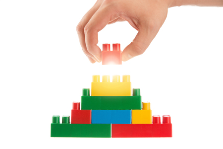 Plastic building blocks and hand, business conception