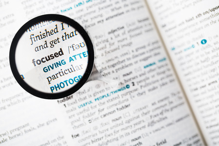 reading glass: Dictionary definition of the word focused and reading glass Stock Photo