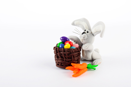 cheeful: Colorful easter eggs in basket, carrots and rabbit isolated on white background