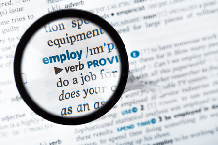 meaning: Dictionary definitions and meaning of the word employ close up and reading glass Stock Photo