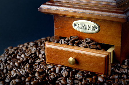 coffee grinder: Vintage coffee grinder and coffee beans isolated over black background