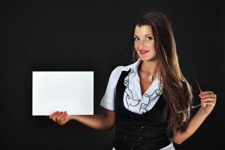 hoja en blanco: Hermosa mujer de negocios sostiene la hoja de papel en blanco y gafas aisladas sobre fondo negro