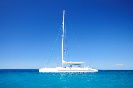 carribean: Beautiful cloudscape and sailing catamaran in the blue carribean sea