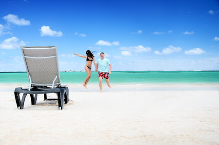 cana: Happy couple and chair relaxing on a tropical beach in Punta Cana, Dominican Republic