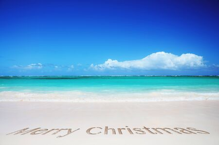 Clear tropical beach and merry christmas text in the sea sand Standard-Bild