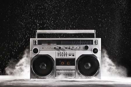 retro radio: 1980s Silver Retro ghetto blaster and dust isolated on black background