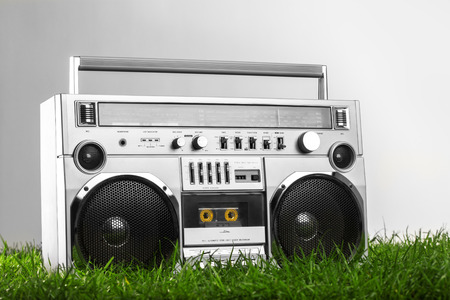 boom box: Retro-styled silver boom box over green grass isolated on gray background