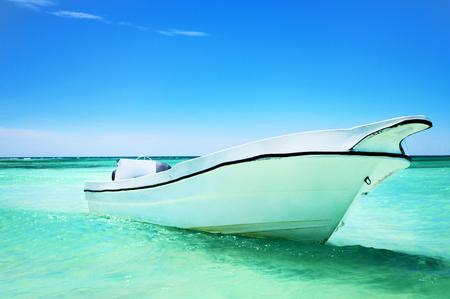 carribean: Boat near the beach in the blue carribean sea and beautiful cloudscape