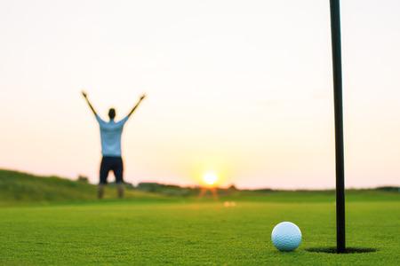 Gelukkig golfspeler op een golfbaan in een luxe resort, zonsondergangschot