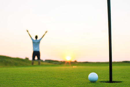 Happy golf player on a golf court at a luxury resort, sunset shot Foto de archivo