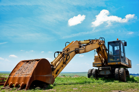 mover: Excavator machine in field. Heavy earth mover and blue sky Stock Photo