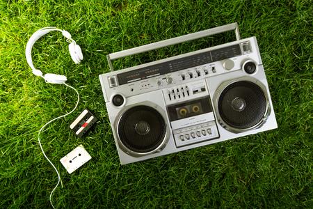 blaster: Retro music blaster and earphones over green grass, studio shot Stock Photo