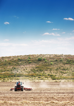 plough land: Agriculture plowing tractor on wheat cereal fields