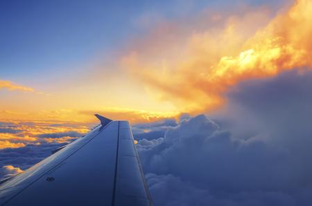 일몰 구름 위를 비행하는 비행기의 날개