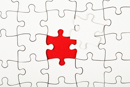 red puzzle piece: Missing piece in a puzzle on red background