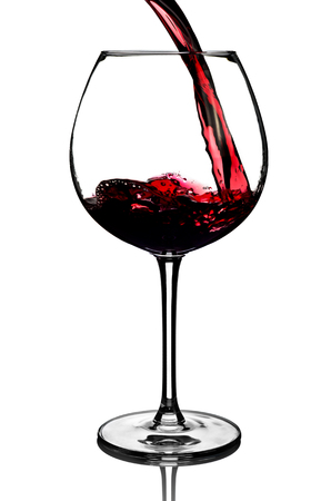 glass of red wine: Red wine pouring into glass isolated on white background