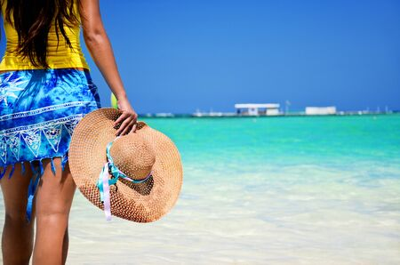 cana: Beautiful woman looking at the sea and enjoying her holiday vacation in Punta Cana, Dominican Republic