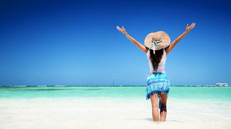 두 팔을 벌려 그녀의 자유를 즐기는 해변에서 편안한 여자 스톡 콘텐츠