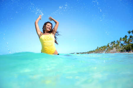 carribean: Happy woman playing with the sea water on exotic carribean beach
