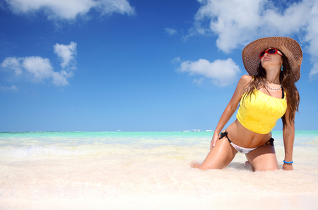 cheeful: Young woman relaxing on beach and enjoying her summer
