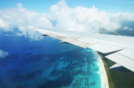View from airplane window. Wing of an airplane flying above the clouds over tropical island Stock Photo