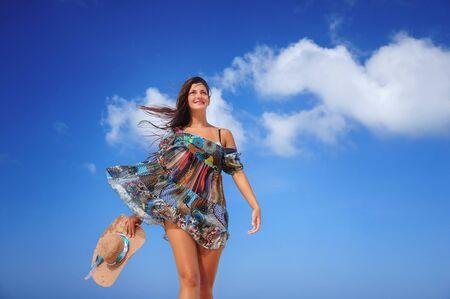 젊은 여자가 이국적인 카리브 해변에서 춤을