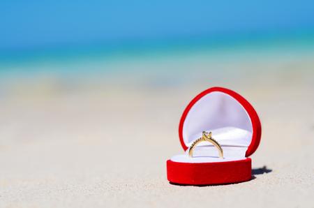 황금빛 결혼 반지는 모래 사장에 스톡 콘텐츠