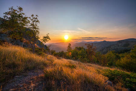 Sunset over mountain hills. Hiking path and green pasture. Bulgaria, Sliven, Karandila