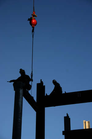 dexterity: Image of two construction workers directing an i-beam into its final position. The red weight of the crane is the only color element in this image except for the sky. Image is not retouched except for removal of workers face for privacy reasons. Stock Photo