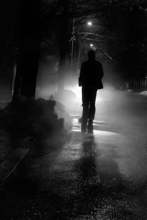 gloomy: Silhouette of a man in front of a bright light outside on a cold winter night.
