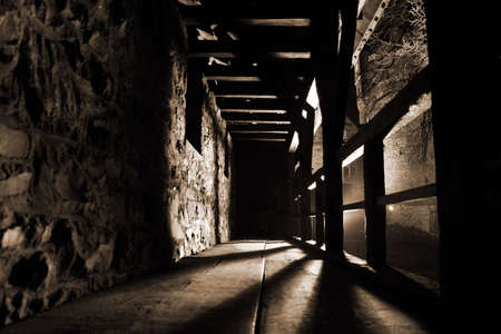 daunting: Inside view of a defensive walkway along the outside walls of the city castle of Altena at night. Strong light and shadows give this image a daunting and mysterious atmosphere.