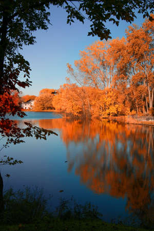 coloful: A fall lake scene like in a picture book. A lonely house overlooking a lake that is swarming with reflections of fall foliage. Stock Photo