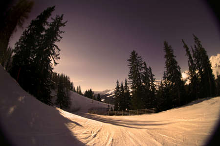 emotive: Fisheye shot of a skiing slope in the alps. Warm tones are intentional to create mood.