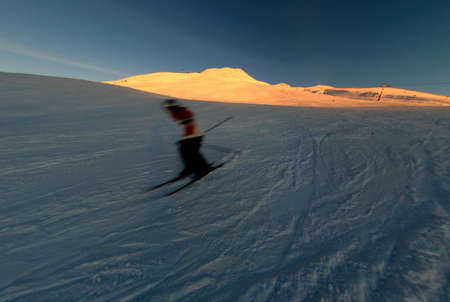 action shot: Action shot of a skier barreling down a slope at sunset. Stock Photo